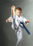 Lo sportivo in karategi sta battendo l'alta gamba diretta di scossa Fotografie Stock Libere da Diritti