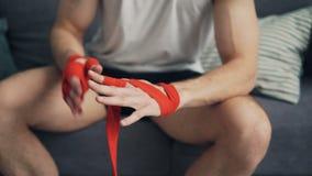 Lo sportivo maschio sta avvolgendo le mani con gli involucri del polso prima della formazione a casa stock footage