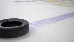 Lo sportivo in pattini con il bastone di hockey batte il disco sulla pista di pattinaggio sul ghiaccio per la partita dell'hockey