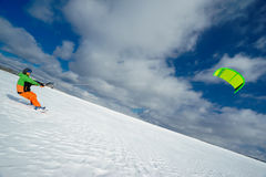 Lo sportivo su uno snowboard esegue l'aquilone Immagine Stock