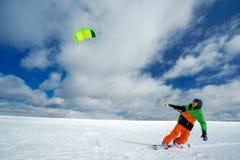 Lo sportivo su uno snowboard esegue l'aquilone Fotografie Stock