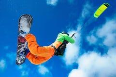 Lo sportivo su uno snowboard esegue l'aquilone Fotografia Stock Libera da Diritti