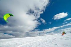 Lo sportivo su uno snowboard esegue l'aquilone Fotografie Stock Libere da Diritti