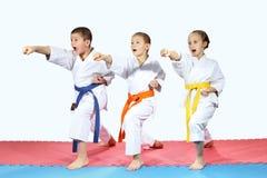 Lo sportivo tre in karategi sta colpendo le armi dei colpi Immagini Stock