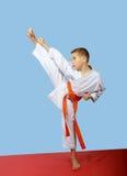 Lo sportivo in un kimono esegue un alto piede del colpo Immagini Stock