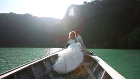 lo sposo abbraccia la sposa che si siede in barca del longtail archivi video