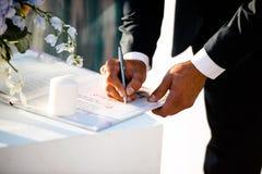 Lo sposo alla cerimonia di nozze mette la sua firma sul documento immagine stock libera da diritti