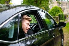 Lo sposo arriva in macchina alla chiesa del villaggio sul suo giorno delle nozze fotografia stock