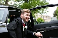 Lo sposo arriva in macchina alla chiesa del villaggio sul suo giorno delle nozze immagine stock libera da diritti