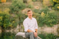 Lo sposo, aspettante affettuoso la sua sposa, sorrisi, un tipo bello attraente sta sedendosi su una pietra in una foresta verde fotografie stock