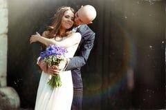 Lo sposo bacia la guancia della sposa che la abbraccia da dietro nei raggi o immagine stock libera da diritti