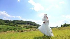 Lo sposo bello felice porta dentro passa la bella sposa bionda nel campo verde soleggiato Paesaggio meraviglioso della molla stock footage