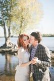 Lo sposo che bacia sposa sulla sponda del fiume Fotografia Stock