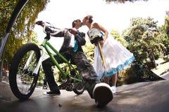 Lo sposo che si siede sulla bicicletta sta baciando la sua moglie immagini stock libere da diritti