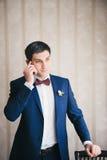 lo sposo chiama per telefono che pende l'altra mano circa una sedia Immagini Stock