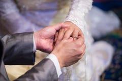Lo sposo chiuso-su indossa la fede nuziale alla sposa Fotografie Stock Libere da Diritti