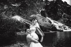 Lo sposo circonda la sua giovane sposa, sulla riva del lago Morskie Oko poland Foto in bianco e nero di Pechino, Cina immagine stock