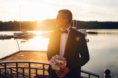 Lo sposo con un mazzo di nozze sta aspettando la sua sposa al tramonto immagine stock libera da diritti