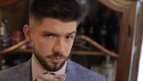 Lo sposo con una barba nera esamina la macchina fotografica Uomo d'affari Farfallino rosa stock footage
