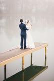 Lo sposo corregge il velo per la sposa che sta sul pilastro Fotografie Stock