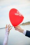 Lo sposo dà un modulo dell'aerostato di cuore alla sposa Fotografie Stock Libere da Diritti