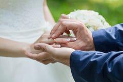 Lo sposo dispone l'anello sul bride& x27; mano di s Primo piano della foto immagini stock libere da diritti