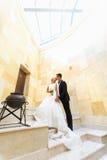 Lo sposo e la sposa baciano la condizione sull'scale bianche nell'ambito di ceil di vetro Fotografia Stock