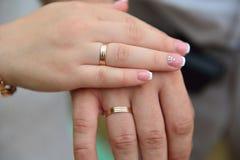 Lo sposo e la sposa mostrano gli anelli Immagini Stock Libere da Diritti