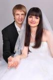 Lo sposo e la sposa tengono le mani ed esaminano la macchina fotografica Fotografie Stock