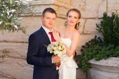 Lo sposo ha abbracciato delicatamente la sposa sulla via immagine stock libera da diritti