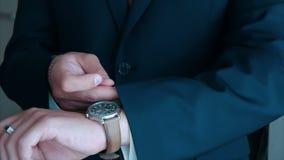 Lo sposo indossa l'orologio sulla sua mano sinistra a nozze video d archivio
