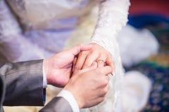 Lo sposo indossa la fede nuziale al dito della sposa Fotografia Stock