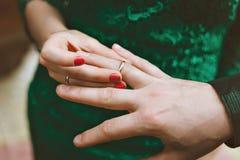 Lo sposo indossa la sposa dell'anello Una donna indossa un anello all'uomo aggancio Fotografia Stock