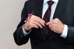 Lo sposo indossa un vestito davanti ad uno specchio Fotografia Stock Libera da Diritti