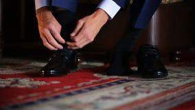 Lo sposo lega i pizzi sulle sue scarpe nere di brevetto video d archivio