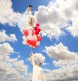 Lo sposo mantiene una sposa sugli aerostati Fotografia Stock Libera da Diritti