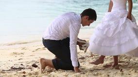 lo sposo mette la scarpa sulla sposa dai capelli lunghi sotto l'albero sulla spiaggia video d archivio