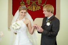 Lo sposo mette solennemente l'anello sulla sposa immagini stock