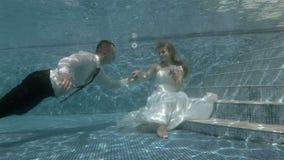 Lo sposo nuota underwater alla sposa che si siede al fondo dello stagno e bacia la sua mano archivi video