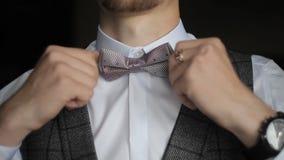 Lo sposo raddrizza una cravatta a farfalla archivi video