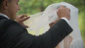 Lo sposo sta sollevando il velo di bella sposa castana sorridente in parco Vista sopra la sua spalla Primo piano archivi video