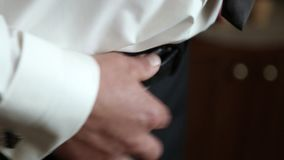 Lo sposo sta vestendosi per le nozze Accessori per la sposa, rivestimento, scarpe, gemelli Un giovane governato si è vestito stock footage