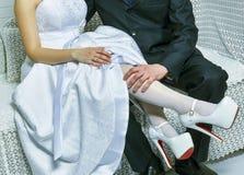Lo sposo tiene la gamba della sposa nel bianco Fotografia Stock Libera da Diritti