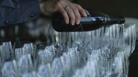 Lo sposo versa il champagne scintillante in calici di vetro stretti che stanno sulla tavola archivi video