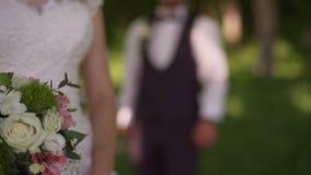 Lo sposo viene ad incantare la sposa bionda con il mazzo dietro lei Movimento lento stock footage
