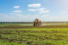 Lo spruzzatore automotore lavora ad un campo sotto un cielo blu con le nuvole fotografia stock