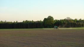 Lo spruzzo del trattore agricolo fertilizza il giacimento di grano con lo spruzzatore dal diserbante dell'antiparassitario archivi video