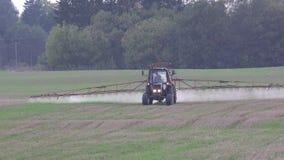 Lo spruzzo del trattore fertilizza il campo dell'azienda agricola con i prodotti chimici del diserbante dell'insetticida 4K video d archivio