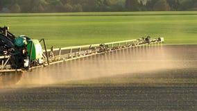 Lo spruzzo del trattore fertilizza il giacimento di grano con lo spruzzatore Il movimento lento tenuto in mano segue stock footage