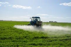 Lo spruzzo del trattore fertilizza il prodotto chimico dell'antiparassitario del campo Fotografie Stock